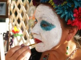 A catrina puts on her face.
