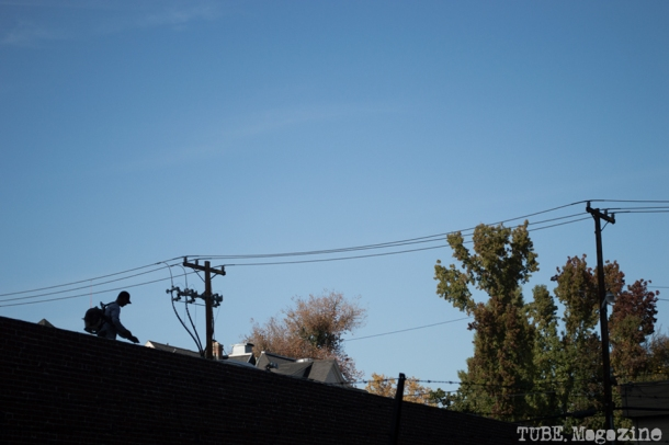 A worker blows leaves and debris off of the roof of a building on I Street. Photo M.Hershenow. 2014.