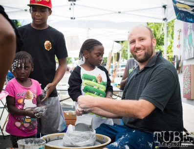 Artist John Klaiber teaching children how to work on the ceramics wheel at the Crocker Block by Block Party in District 5, July 9, Sacramento CA. Photo Melissa Uroff